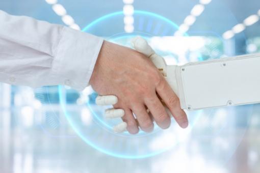 人間とロボットが握手している