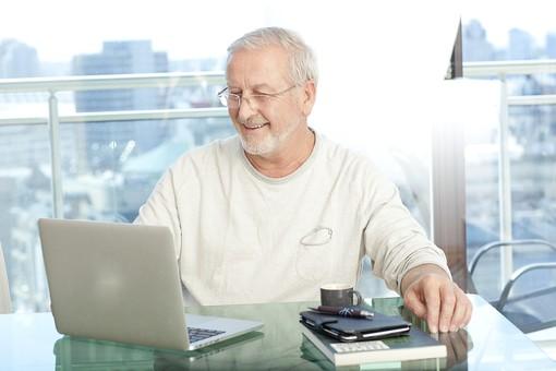 パソコンの前でシニア世代が微笑んでいる