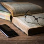 テーブルの上の本とメガネとスマホ