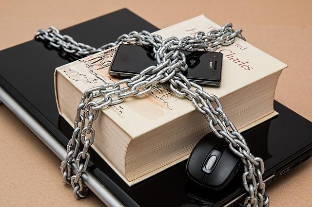 鎖で締められたパソコンとスマホ