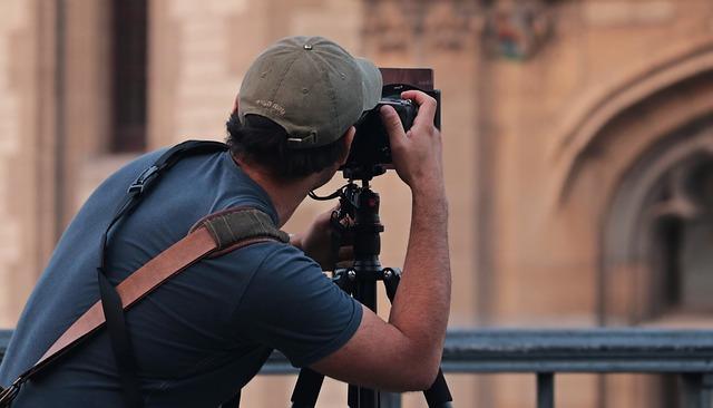 カメラのレンズをのぞいている男性