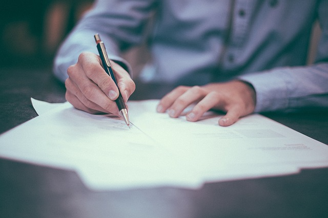 男性が書類を書いている