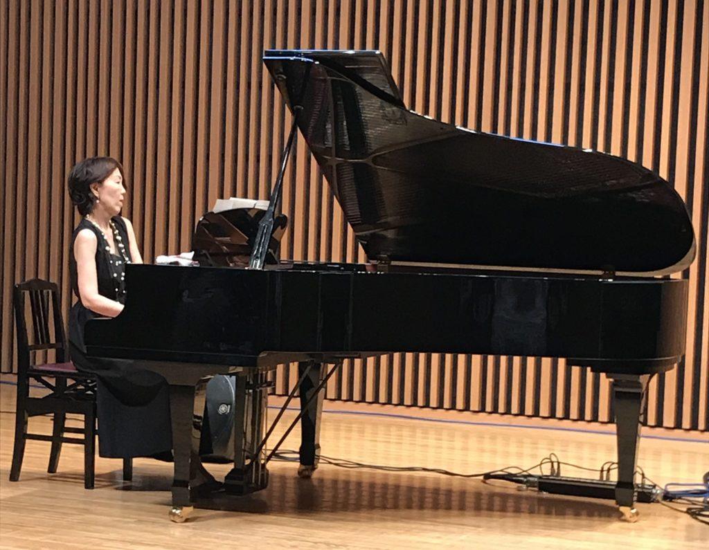 グランドピアノを見弾く黒いドレスの女性